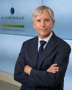 Photographe portrait corporate lyon corporate M. Kirk Ririe avec logo Biomerieux en arriere plan a lyon